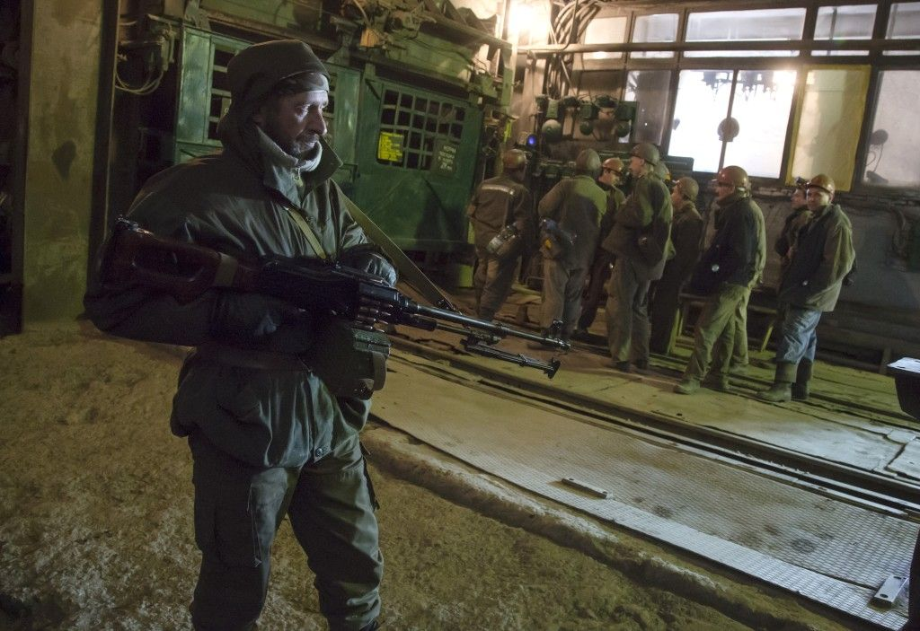 In this photo taken on Oct. 30, 2014, a pro-Russian rebel stands guard as miners prepare to go into an elevator at the Chelyuskintsev coal mine in the city of Donetsk, eastern Ukraine. Pro-Russian rebels often threaten to stop sending coal to Kyiv but the Ukrainian government could simply cut off the electricity generated at a power station on its side. Without that power, shafts will get flooded and could be lost entirely as an energy source. Dmitry Lovetsky/AP Photo