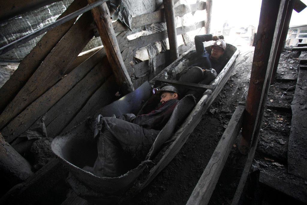 """Sergei Ivanov and Vovka hunched over in a canoe-like vessel that they call the """"Boat"""" that will take them 390 feet below ground level inside this illegal mine in Shahtersk, eastern Ukraine on April 28, 2014. During their eight-hour shift they dig out and send up about 15 – 20 """"boat"""" loads, between them they make about the equivalent of only three US dollars for every load they told me.  Two month ago, they lost a friend and fellow miner at another illegal mine when the steel cable attached to the """"Boat"""" snapped and the miner fell to his death deep underground. (Ghazi Balkiz/ NBC News)"""